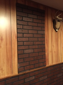 All wrong! Faux brick paneling nailed to faux wood paneling to cover the electrical box.