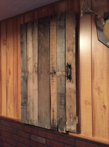 The reclaimed wood door looks great and it practical. Now, about the faux wood paneling...